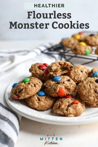 gluten free monster cookies on white plate with m&m cookies on cooling rack in backgroud