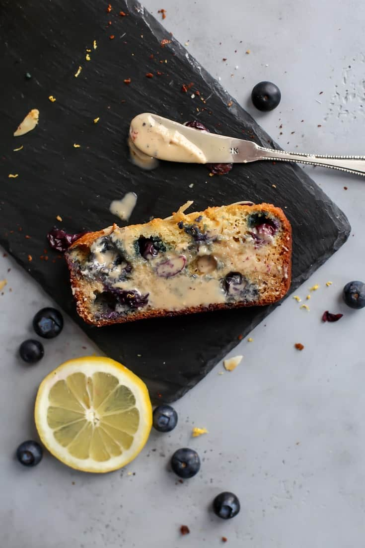 Lemon Blueberry Bread on slate with buttered knife and lemon slice