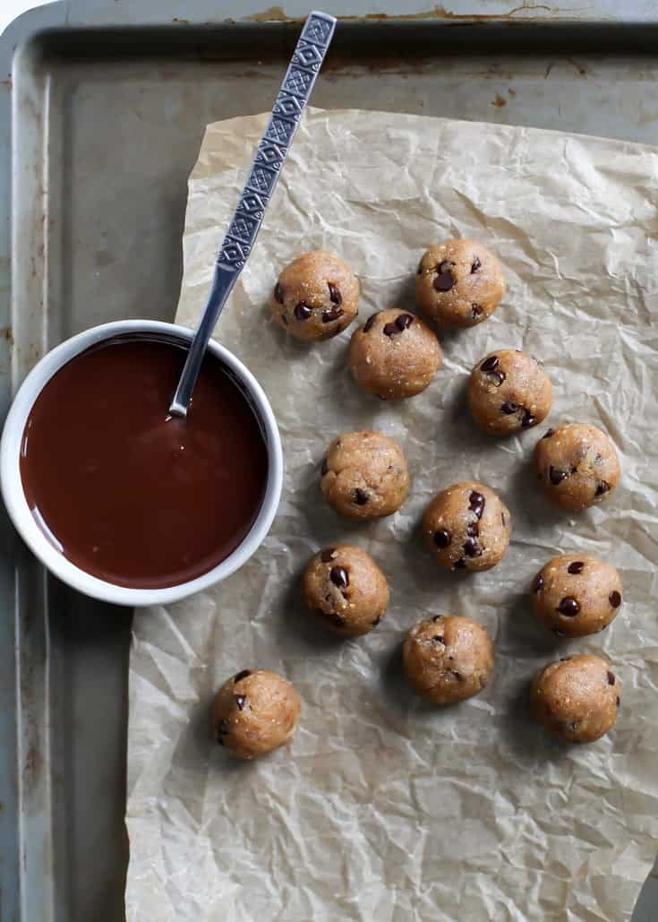 raw paleo cookie dough balls on parchment paper baking sheet with melted chocolate in bowl