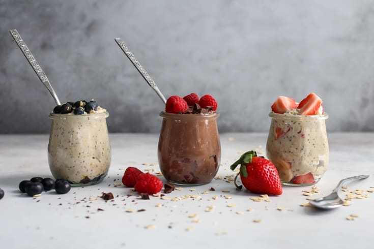 Overnight Oats with fresh berries in tulip jars with spoons