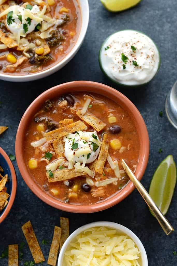 soup in an orange bowl with sour cream and tortilla chips