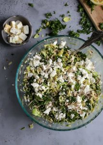feta topped Shredded Brussels Sprouts Quinoa Kale Salad in bowl with serving spoon