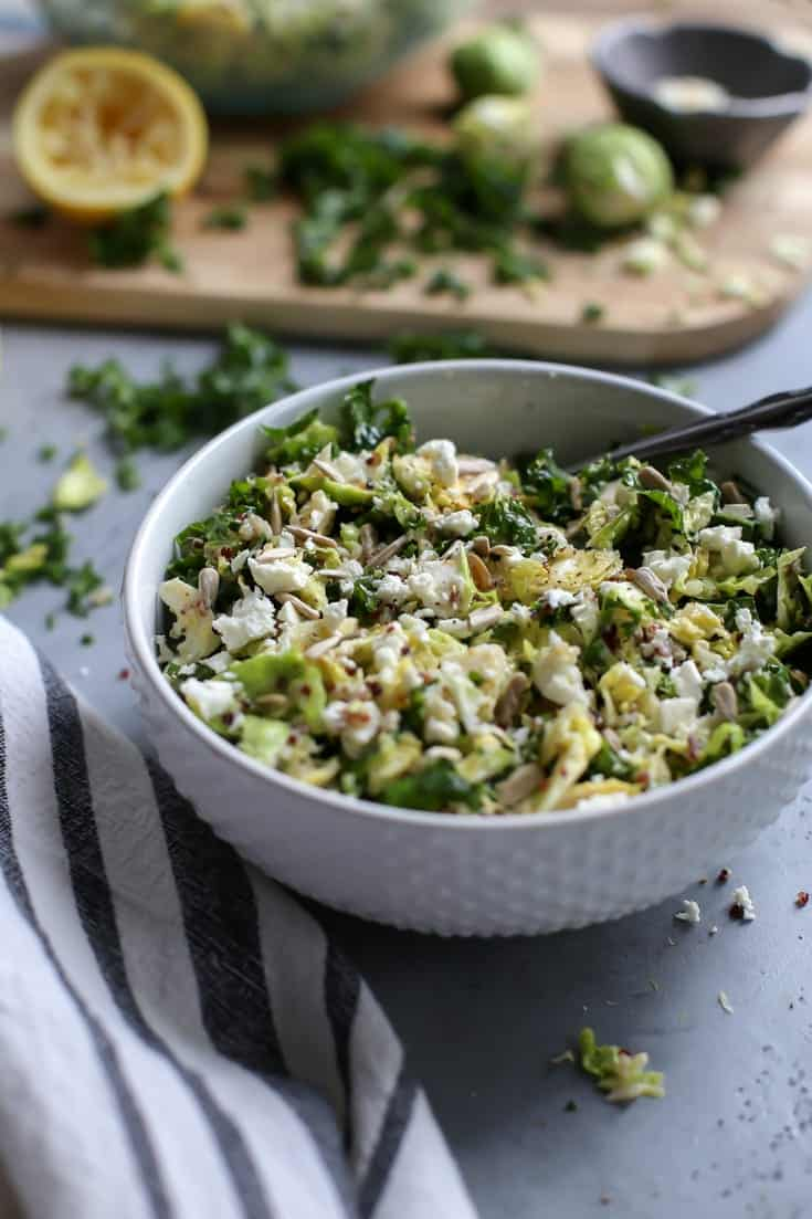 bowl of kale quinoa salad with lemon, brussels sprouts and feta