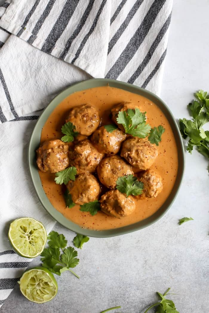 Red curry meatballs on plate with cilantro and lime