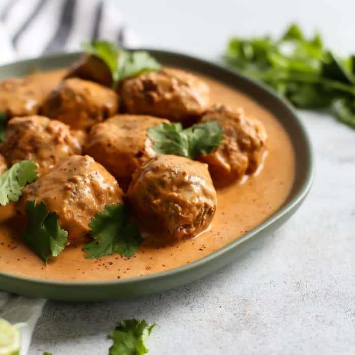 Up close red curry turkey meatballs on place with cilantro garnish