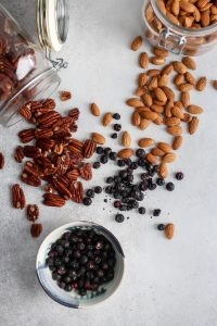 jar of pecans, almonds and bowl of freeze dried blueberries for homemade almond pecan butter
