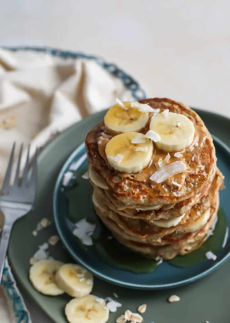 stack of banana peanut butter layered banana pancakes on green plates