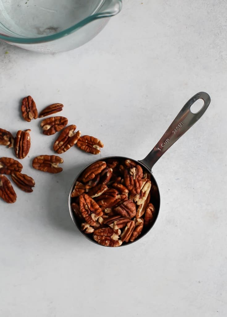 measuring spoon with raw pecans for homemade nut milk