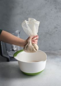 Squeezing nut milk bag to strain nut pulp from milk.