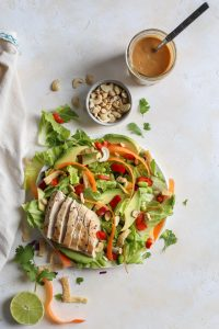 cashew pieces in small dish, thai peanut dressing in jar, grilled chicken thai salad o plate with napkin
