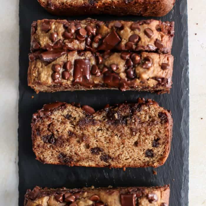 sliced banana bread with chocolate chips on slate tray and white board