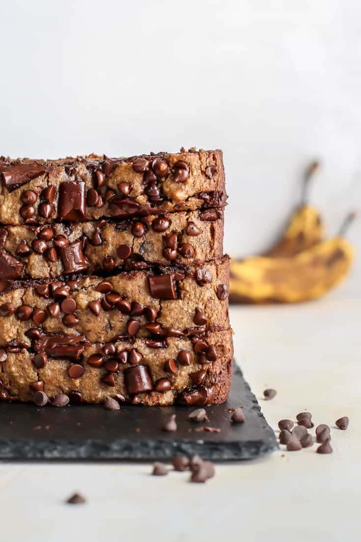 stacked banana bread with chocolate chips placed on slate tray, extra ripe bananas