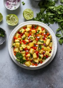 bowl of pineapple salsa on white plate with limes and cilantro