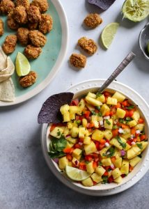 bowl of pineapple salsa with chip and fish taco bites