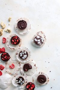 strawberry cashew butter stuffed chocolate cups on white board with freeze dried strawberries, coconut and cashews