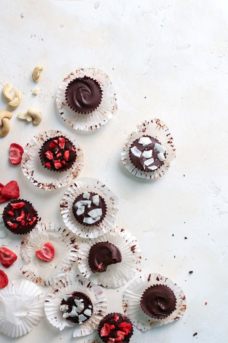 chocolate strawberry cashew butter cups on white board with freeze dried strawberries, coconut and cashews