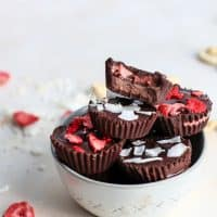 strawberry cashew butter stuffed chocolate cups in bowl with freeze dried strawberries