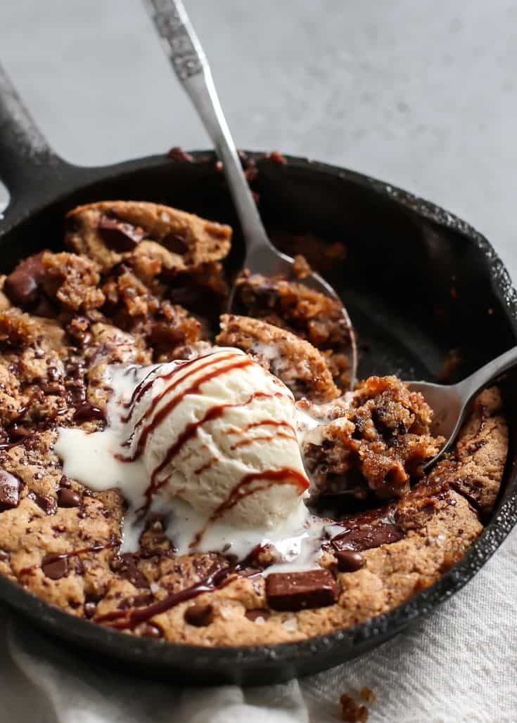 two spoons digging into a chocolate chunk cookie in cast iron skillet topped with ice cream