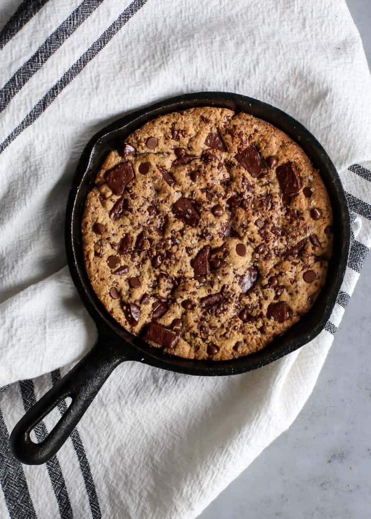 salted chocolate chunk skillet cookie in cast iron skillet on towel