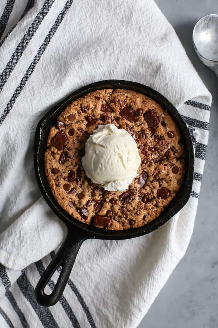 scoop of vanilla bean ice cream on chocolate chunk cookie in cast iron skillet