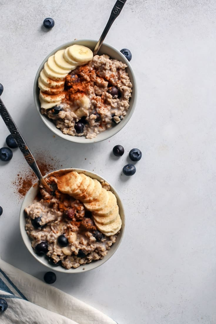warm blueberry banana oatmeal in bowls topped with cinnamon