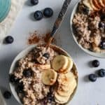 warm blueberry banana oatmeal in bowls with coffee mug