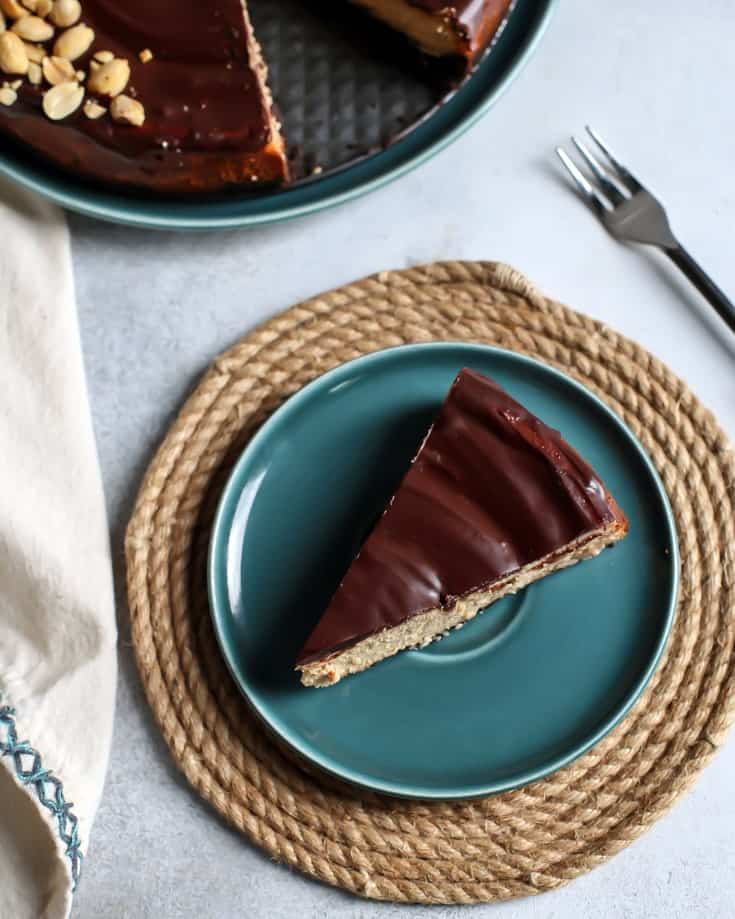 piece of peanut butter cheesecake with chocolate ganache on plate
