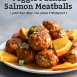 salmon meatballs with orange glaze. orange slices and green onion garnish on plate