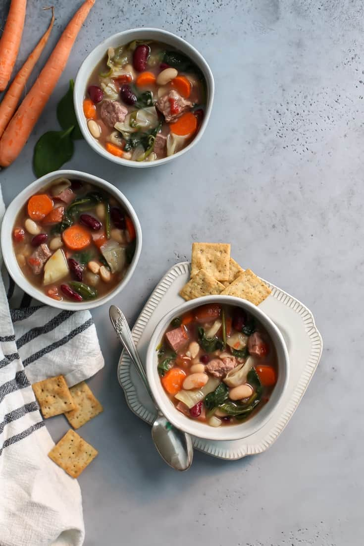 bowls of portuguese soup with crackers on plate
