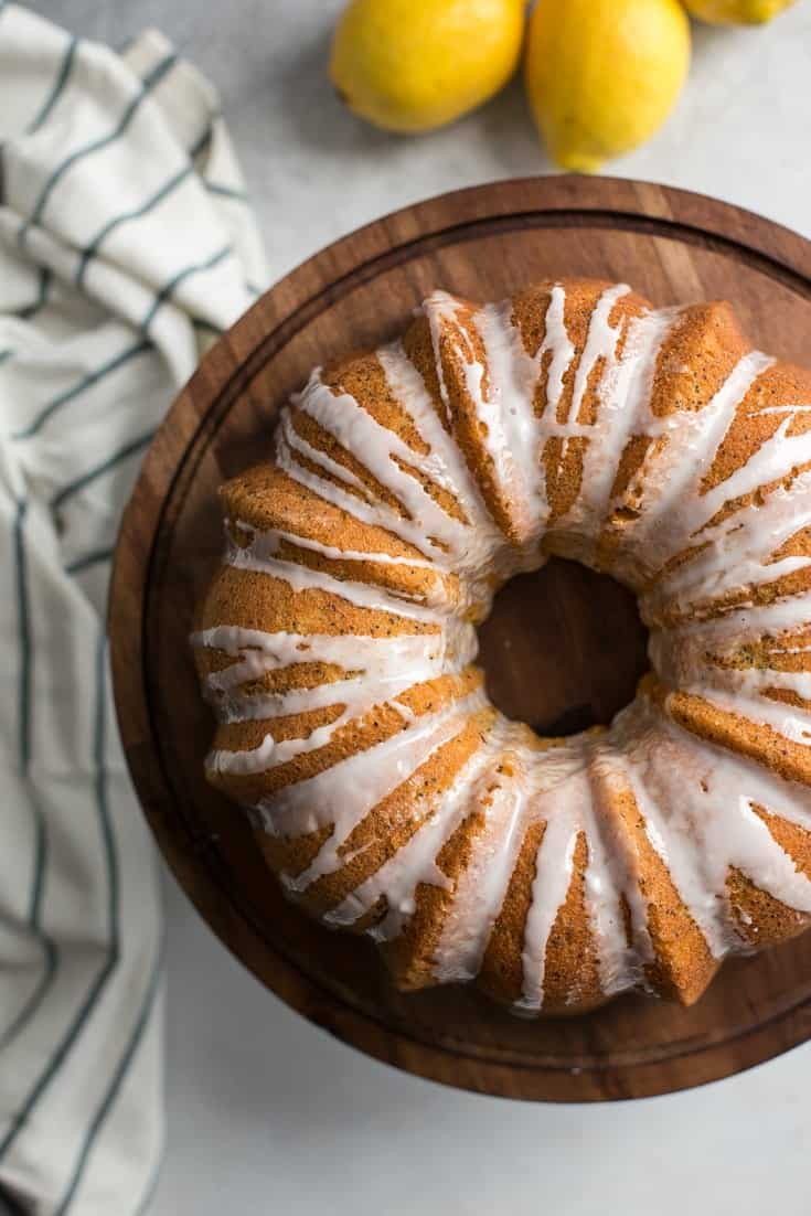 lemon poppy seed bundt cake with glaze on wooden cake stand with lemons