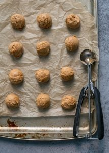 cashew butter dough on cookie sheet with small cookie scoop for cashew butter eggs