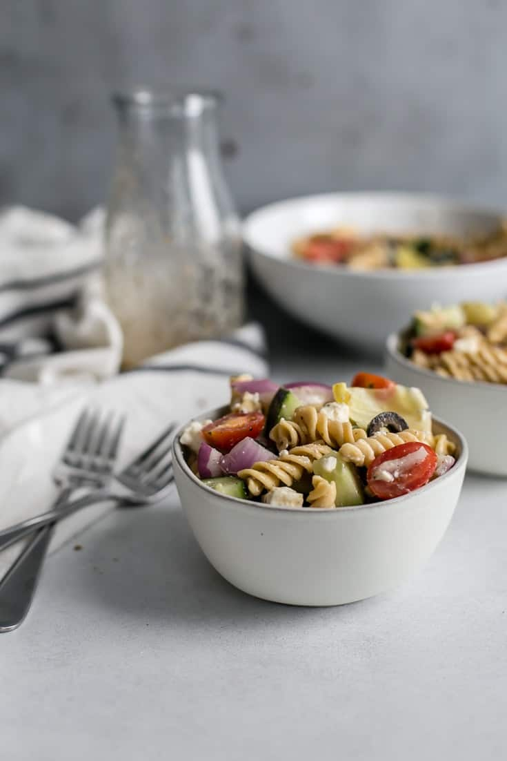 small bowls of Greek pasta salad with dressing jar and forks