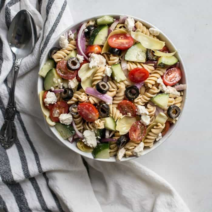 bowl of greek pasta salad on towel with spoon