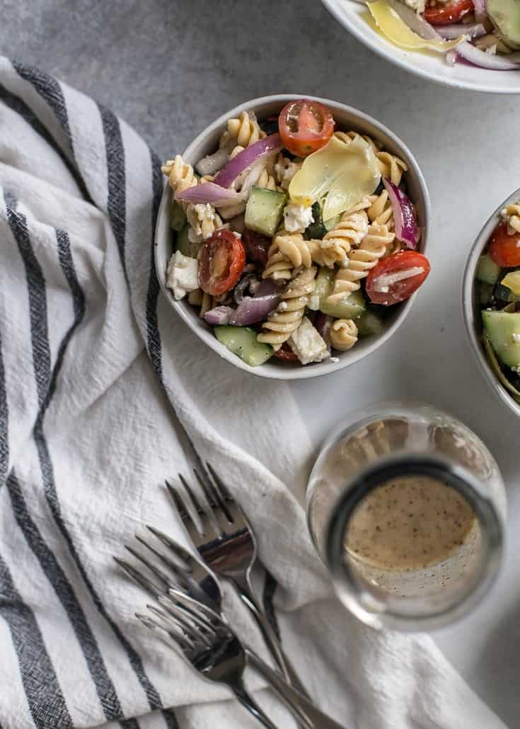 bowls of healthy greek pasta salad with dressing bottle and forks
