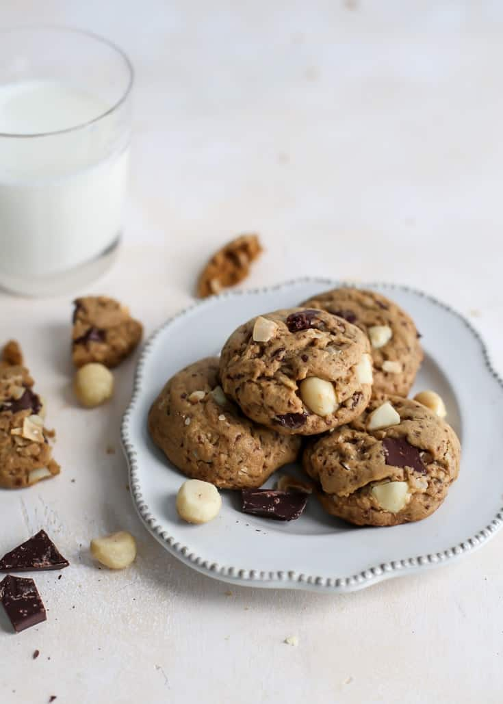 plate of macadamia nut cookies with glass of milk and chocolate chunks