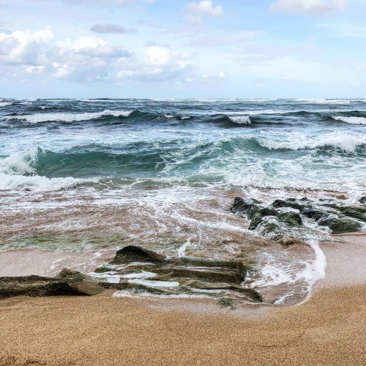 waves splashing on rocks in kauai