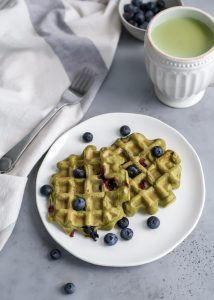 plate of matcha waffles with blueberries and melted coconut butter