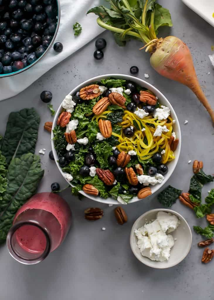 bowl of kale salad with spiralzed golden beets and blueberry dressing