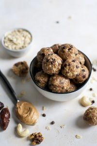maca peanut butter energy balls in bowl with peanut butter on spoon and oats in mini bowl