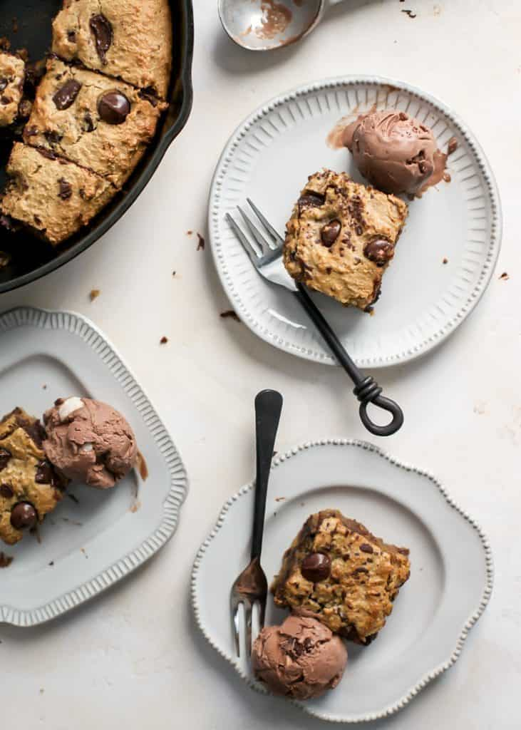 pieces of banana chocolate chip skillet cake on white plates with chocolate ice cream