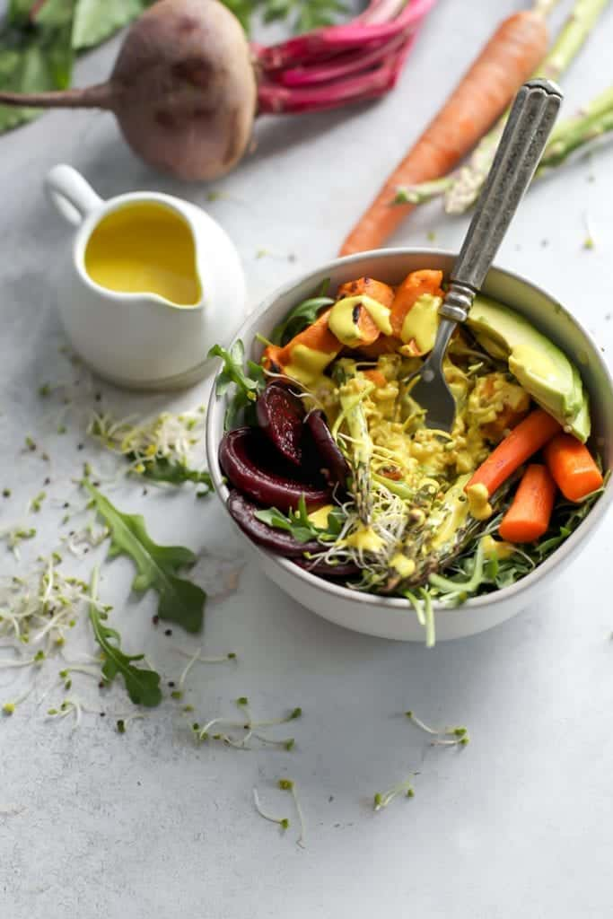 bowl or roasted spring veggies with turmeric tahini dressing in small pitcher for a spring power bowl