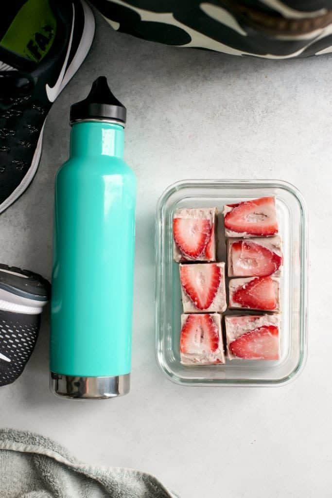 turquoise water bottle, gym bag, shoes and strawberry freezer fudge in meal prep container