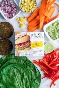 Dr. Praeger's Tex Mex Veggie Burger Wraps with carrots, corn, red bell pepper, guacamole, red onion, and collard greens on marble slab