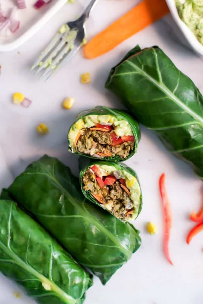 veggie burger collard wraps cut open on marble slab