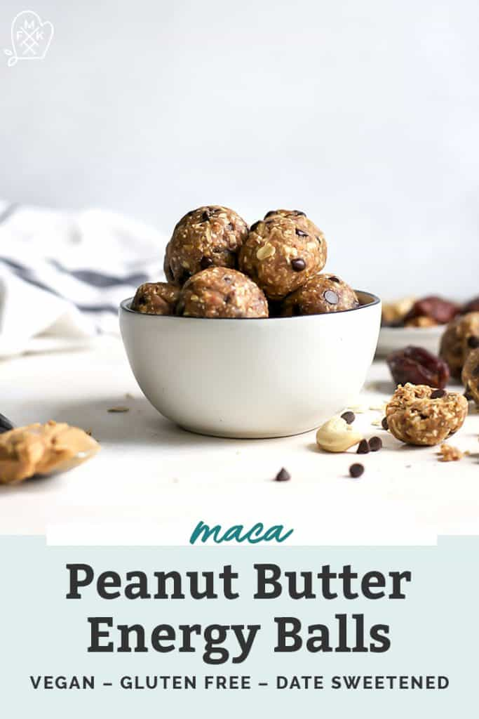 Bowl of maca peanut butter energy balls with chocolate chips and peanut butter strewn on counter