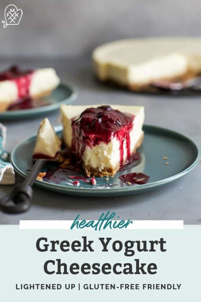 healthier greek yogurt cheesecake with berry compote on teal plate with strawberry and blueberries in background