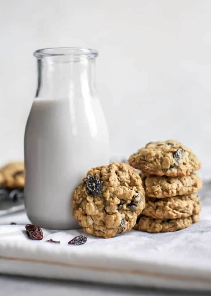 oatmeal raisin cookies stacked next to glass bottle of milk