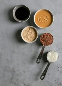 bowl of peanut butter, maple syrup, maca powder in small dish, cocoa powder in measuring cup, coconut oil in measuring cup