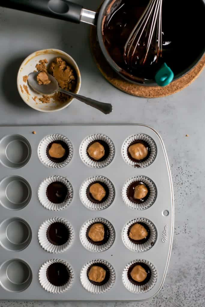 mini muffin pan with homemade peanut butter cups, homemade chocolate in sauce pan with whisk and a bowl of maca peanut butter filling