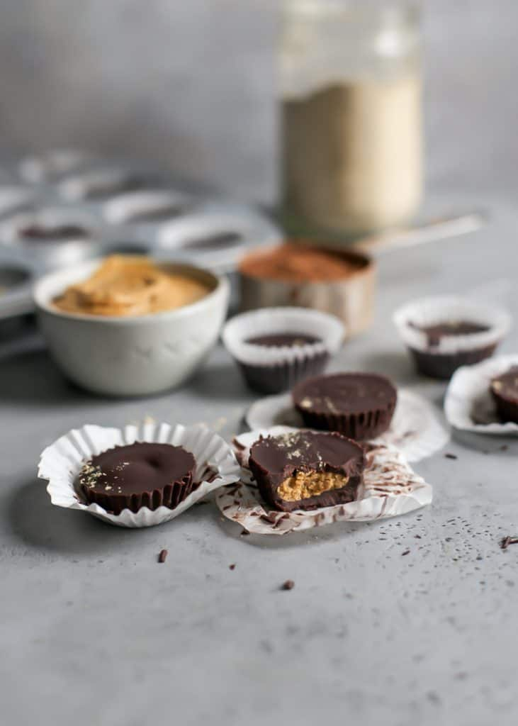 homemade peanut butter cups on paper wrappers with peanut butter and a muffin tin in background